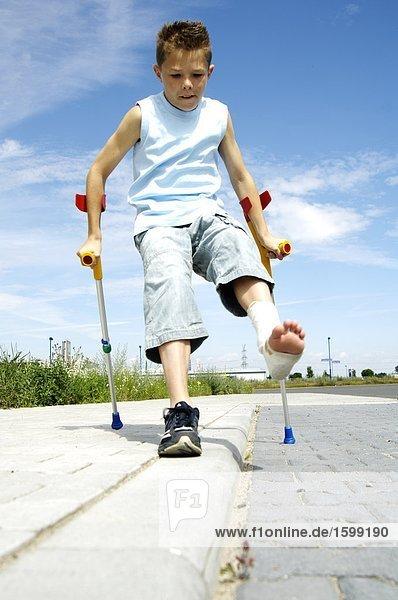 Untersicht jungen zu Fuß unterwegs mit gebrochenem Bein