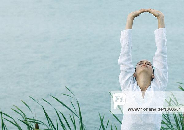 Frau Dehnung Arme über Kopf, See im Hintergrund