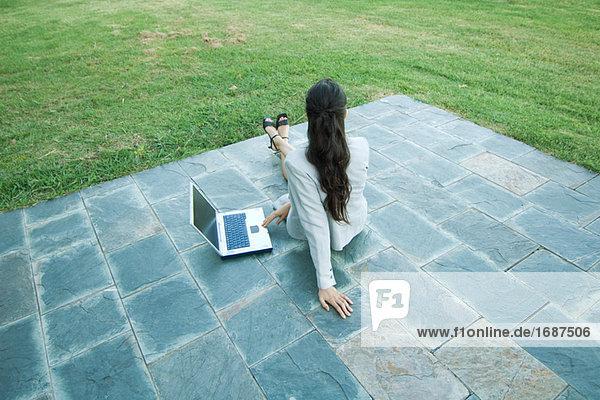 Geschäftsfrau sitzt auf Patio mit Laptop  Wegsehen  Vogelperspektive  Rückansicht