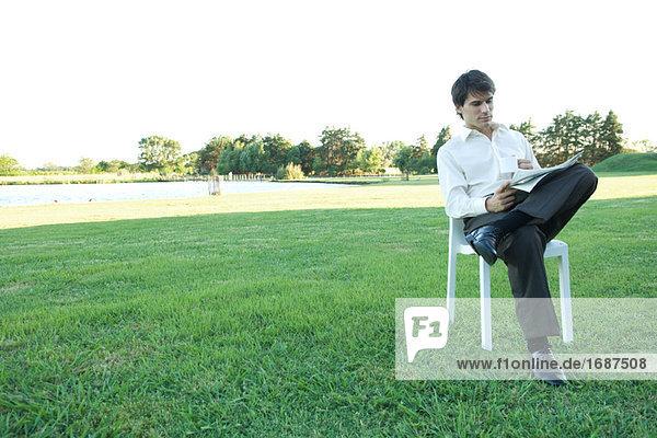 Kaufmann sitzen in Stuhl  auf Rasen  Zeitung lesen und hält mug