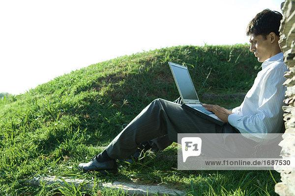 Kaufmann auf Boden  saßen mit laptop