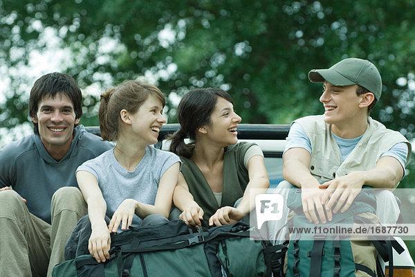 Gruppe von Wanderern sitzen auf der Rückseite des Kleinlastwagen