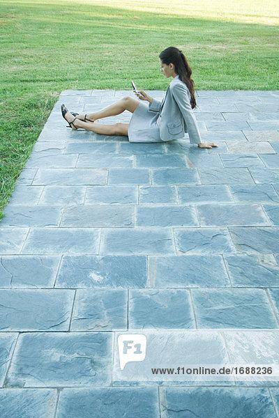 Geschäftsfrau auf Boden auf Patio  saßen mit Handy