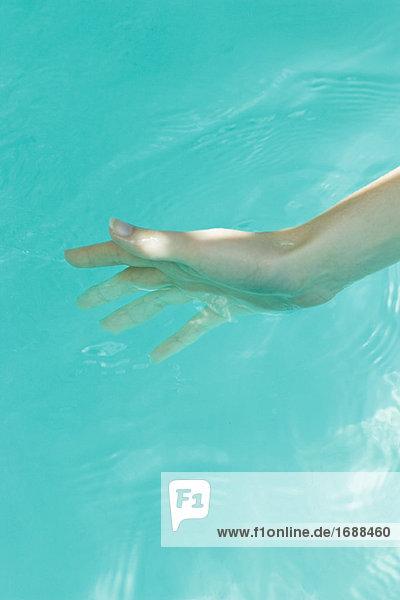 Junge Frau Eintauchen Hand ins Wasser  Nahaufnahme