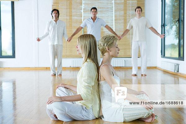 Gruppentherapie  zwei Frauen sitzen während drei Erwachsene Rücken an Rücken halten Hände im Hintergrund