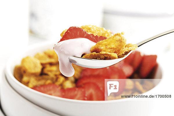 Cornflakes und Erdbeeren auf Löffel  Nahaufnahme