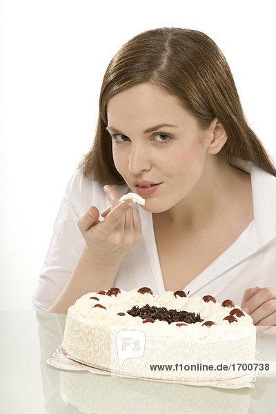 Junge Frau knabbert Kuchen  Portrait