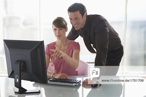 Geschäftsfrau und -mann bei der Arbeit am Computer  Teamarbeit