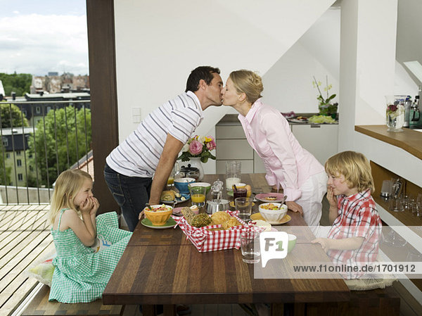 Family at breakfast table  parents kissing