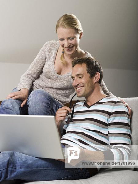Paar auf dem Sofa sitzend  mit Laptop