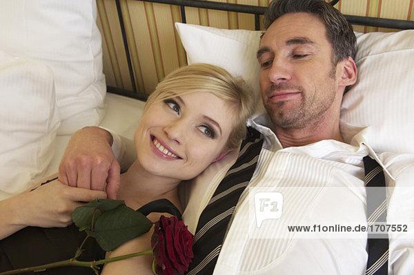 Paar mit einer Rose liegt im Bett  fully_released