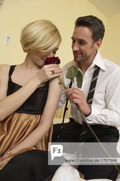 Paar im Bett  Frau riecht an einer Rose  fully_released