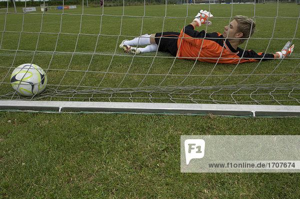 Goalkeeper lying on ground  ball in net