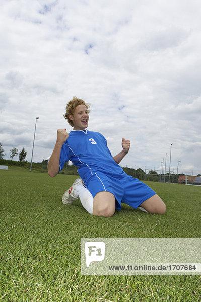 Jubelnder Fußballspieler kniet auf dem Rasen  fully_released