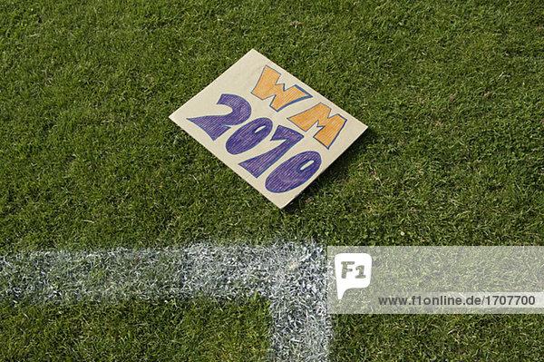 Schild mit der Aufschrift WM 2010 auf einem Fußballrasen  fully_released