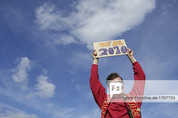 Fußballfan hält ein Schild mit der Aufschrift WM 2010 nach oben  fully_released