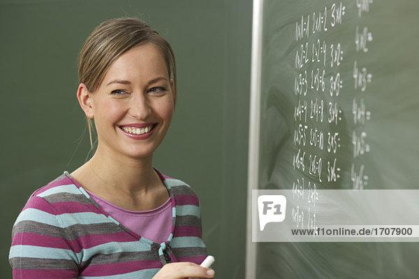 Eine Frau steht vor einer Tafel mit Kreide in der Hand  fully_released
