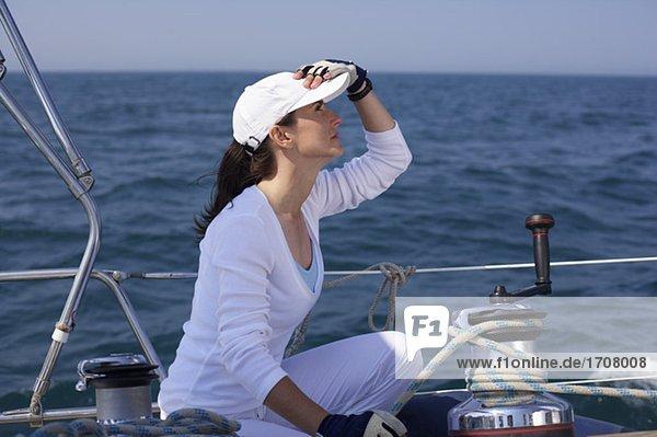 Frau hockt auf dem Deck einer Jacht  fully_released