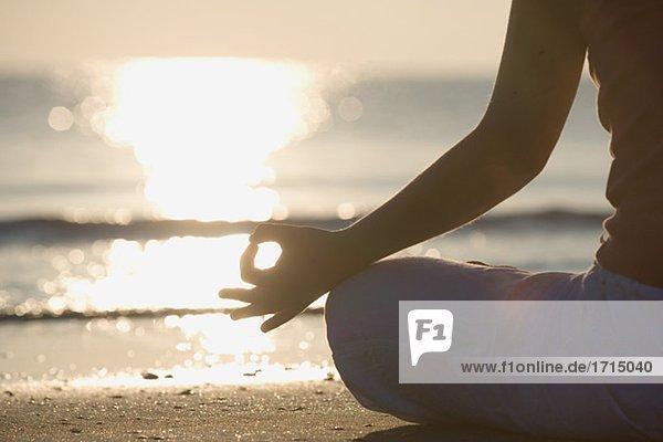 Frau meditieren am Strand