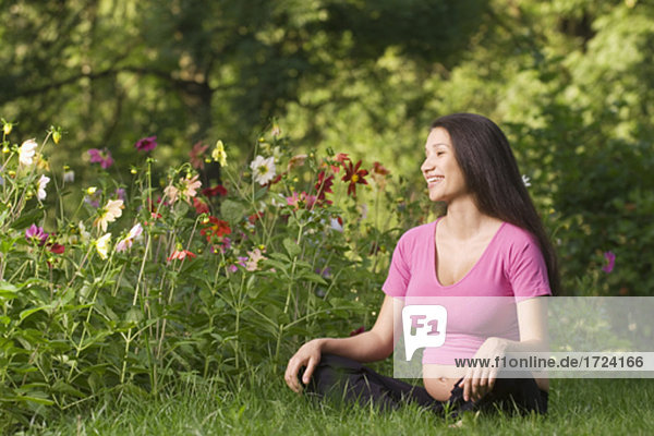 portrait of pregnant young woman sitting on meadow in park