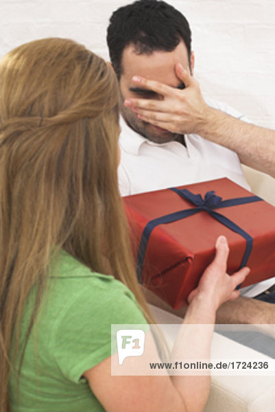 young woman giving present to man