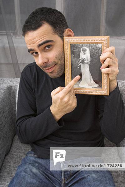 Porträt der jungen Mann  der Fotografie Frau in Hochzeitskleid hält