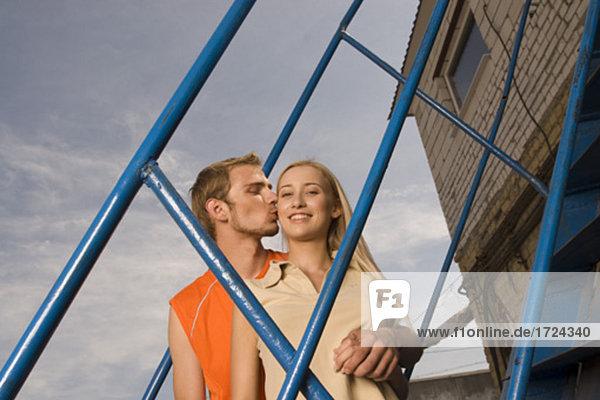 junges paar stehend auf Treppen Mann küssen Frau auf Wange