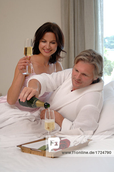 Couple in bed with champagne