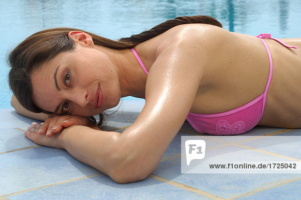 Woman is lying at the swimming pool