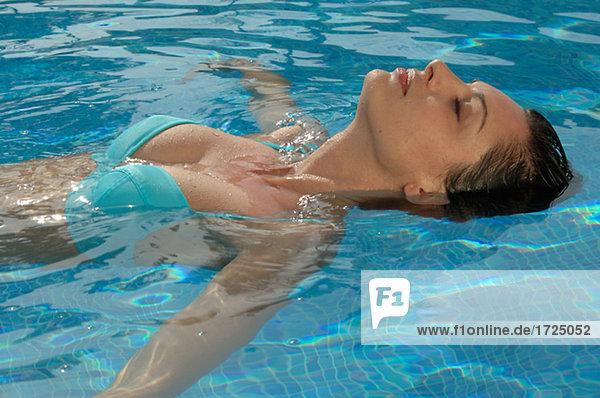 Frau schwimmt im Wasser auf dem Rücken