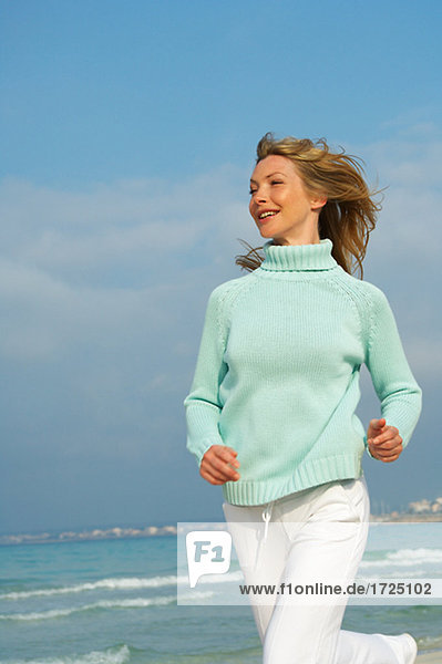 Running woman in turquoise pullover at the sea