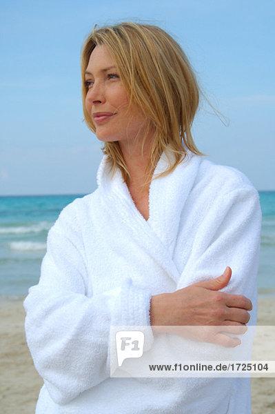 Woman in a bathrobe at the sea
