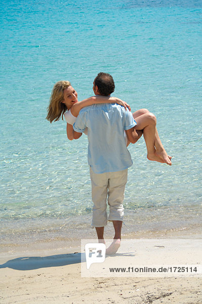 Couple on the beach - man is carrying woman