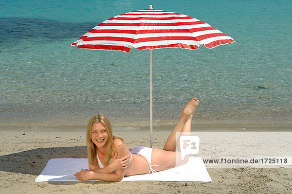 Woman lying on the beach under a sunshade