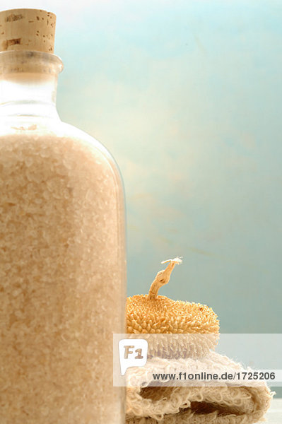 A bottle of bath salts and other bathing utensils