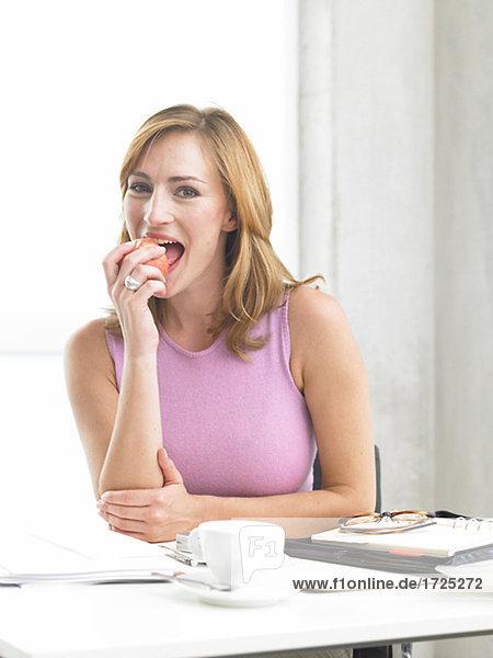 Frau sitzt am Schreibtisch und isst einen Apfel