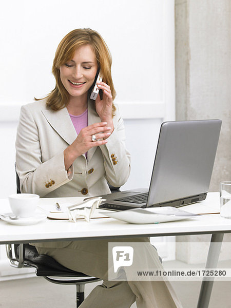 Geschäftsfrau sitz am Schreibtisch und telefoniert