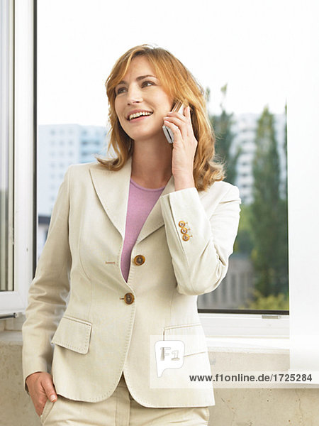 Geschäftsfrau steht am Fenster und telefoniert
