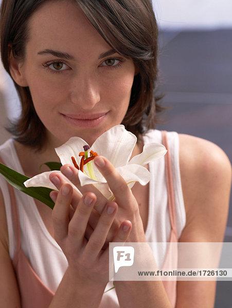 Frau trägt mit einer Lilienblüte