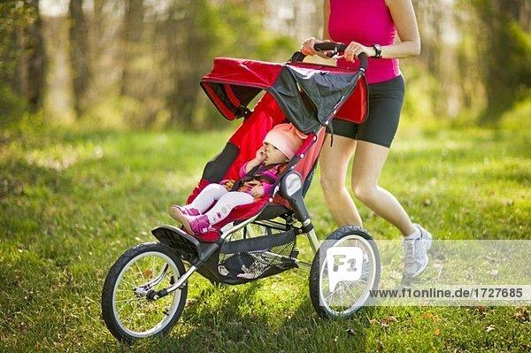 frau joggen mit baby in einem jogging kinderwagen lizenzfreies bild bildagentur f1online 1727685. Black Bedroom Furniture Sets. Home Design Ideas