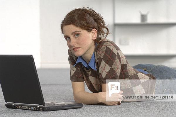 Geschäftsfrau Verlegung auf dem Boden und Laptop verwenden