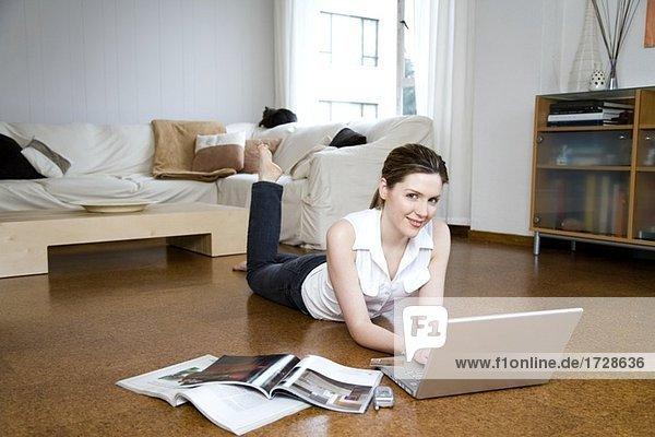 Junge Frau auf Boden mit Laptop liegen