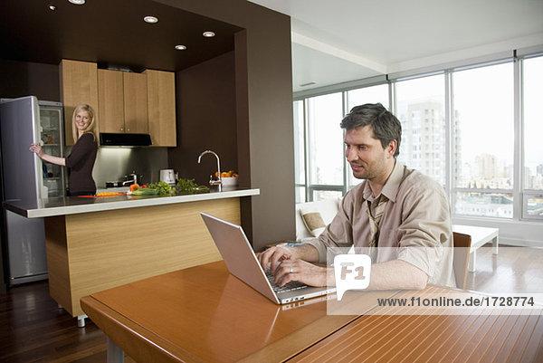 Frau Kochen als Ehemann verwendet Laptop am Tisch