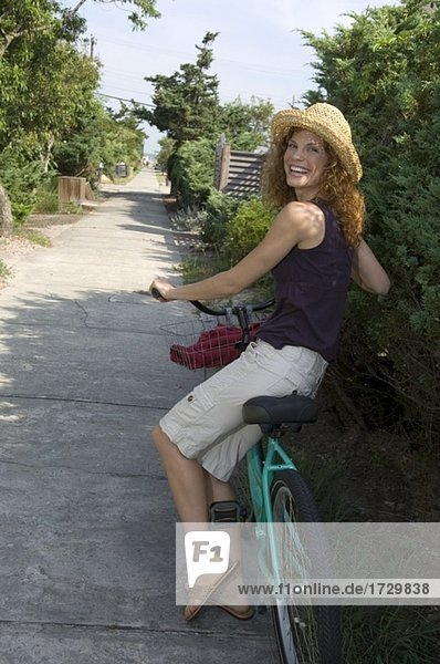 Frau zu Fuß mit Fahrrad und lächelnd Außenaufnahme