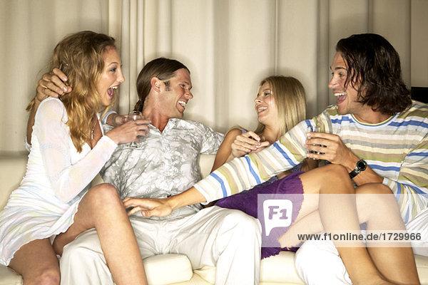 Freunde mit Getränke auf sofa