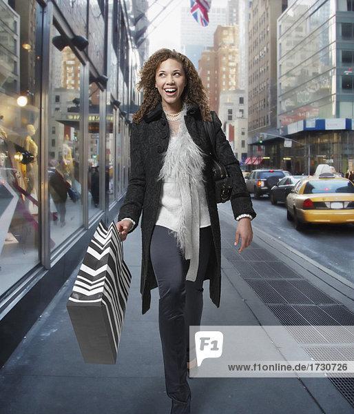 Woman carrying shopping bags down urban street