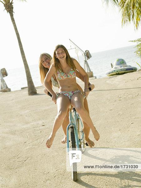 Teenager in Bikinis mit dem Fahrrad am Strand