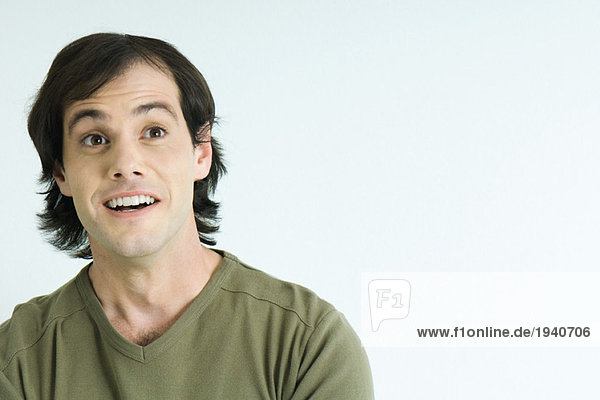 Mann hebt die Augenbrauen  lächelnd  Portrait