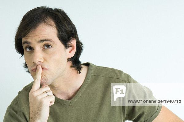 Mann mit Finger über den Lippen  nach oben schauen  Augenbrauen heben  Portrait