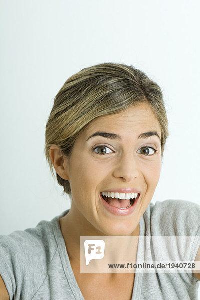 Junge Frau lächelt und hebt die Augenbrauen  Porträt